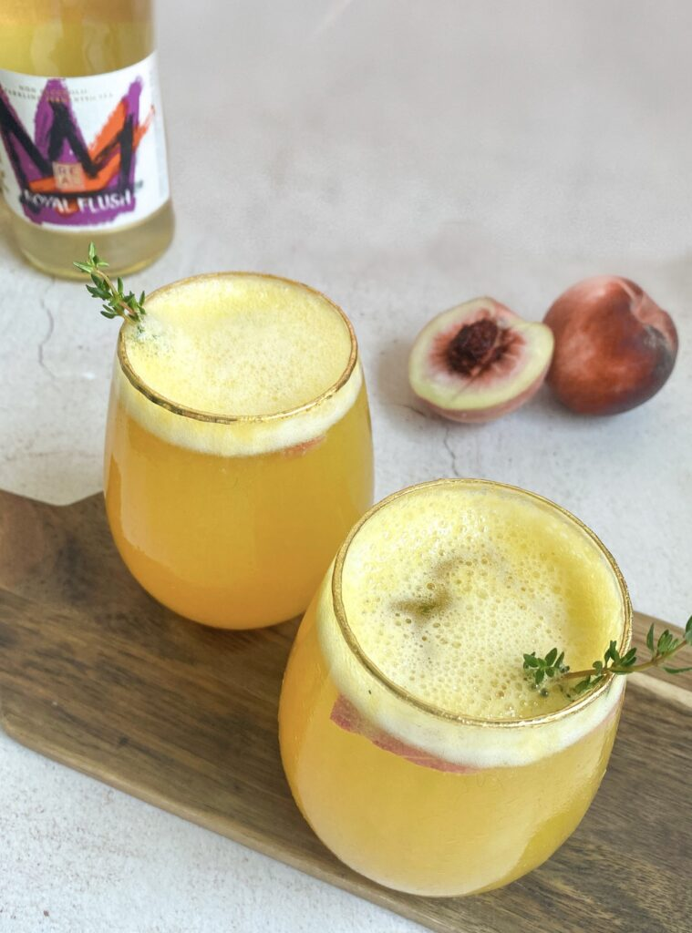 Kombucha cocktails with fresh thyme springs. Peaches and kombucha bottle next to them.